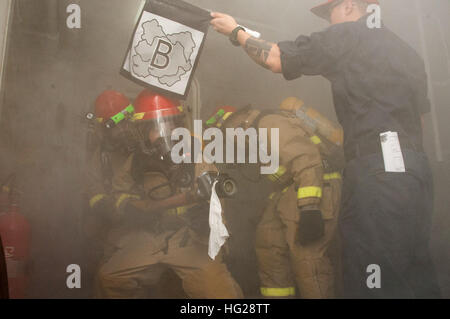 150709-N-YD641-164 TIMOR SEA (July 9, 2015) Sailors practice firefighting techniques during a simulated fire in - Stock Photo