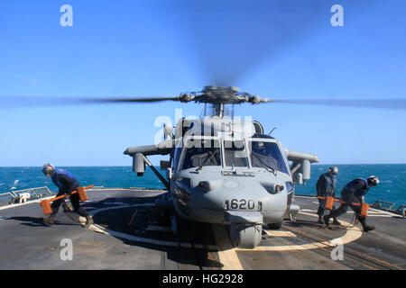 150717-N-BX824-085 TIMOR SEA (July 17, 2015) Sailors remove chocks and chains from an MH-60S Seahawk from the 'Golden - Stock Photo