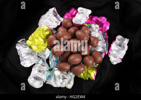 Pile of Chocolate easter eggs unwrapped from the colorful foil wrappers against a black background. - Stock Photo