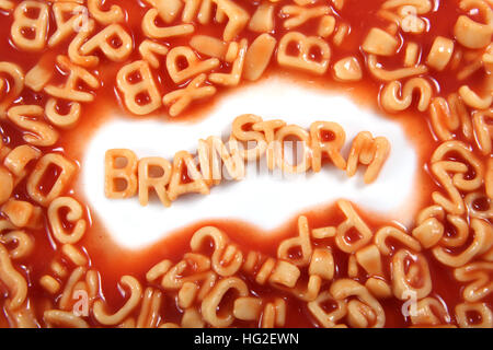 The word 'Brainstorm' written in alphabetti spaghetti, orange pasta shaped letters. - Stock Photo