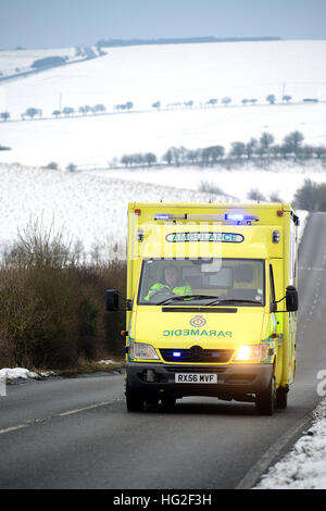 Ambulance on a country road surrounded by snow in winter. - Stock Photo