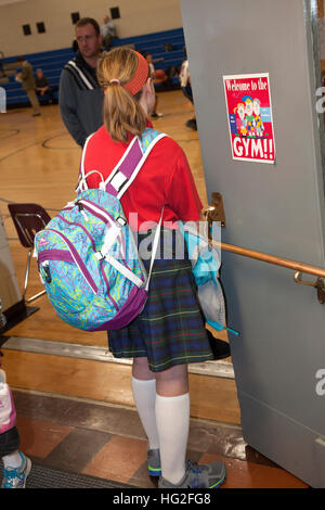 Young teen girl with backpack secretly watching boys play basketball in school gymnasium. St Paul Minnesota MN USA - Stock Photo