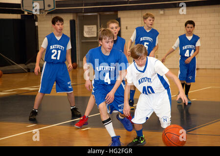 Young teen boys age 13 playing basketball in school gymnasium St Paul Minnesota MN USA - Stock Photo