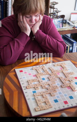 Attractive mature woman studying her next move in a scrabble game. Downers Grove Illinois IL USA - Stock Photo