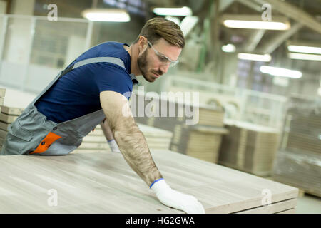 Handsome young man working in the furniture factory - Stock Photo