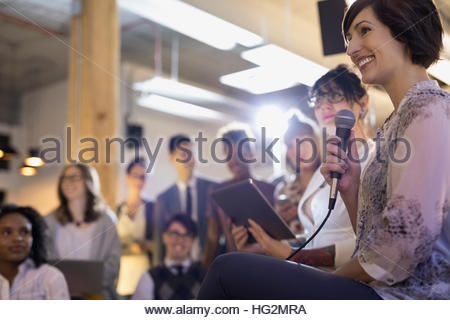 Smiling businesswoman with microphone and digital tablet leading conference meeting - Stock Photo