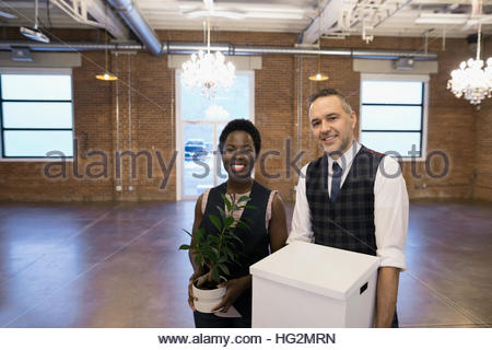 Portrait confident businessman and businesswoman carrying belongings in empty new office - Stock Photo