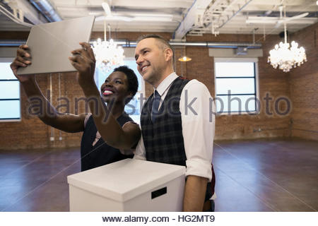 Businessman and businesswoman taking selfie with digital tablet camera in empty new office - Stock Photo