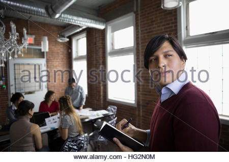 Portrait pensive male designer taking notes in conference room - Stock Photo