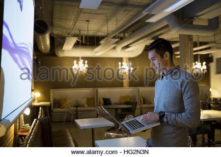 Focused businessman using laptop preparing audio visual presentation in office - Stock Photo