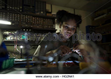 Focused female engineer working with electronics in dark workshop - Stock Photo