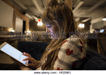 Focused businesswoman working late at digital tablet in office - Stock Photo