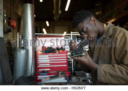 Engineer assembling electronics component in workshop - Stock Photo