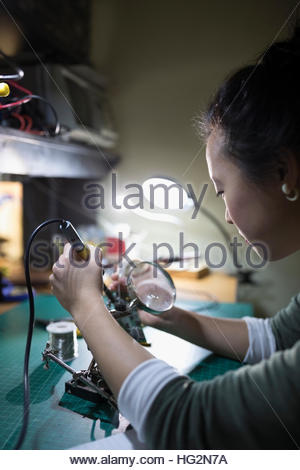 Female engineer using soldering iron assembling electronic components in workshop - Stock Photo