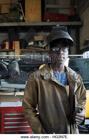 Portrait confident welder wearing protective workwear in workshop - Stock Photo