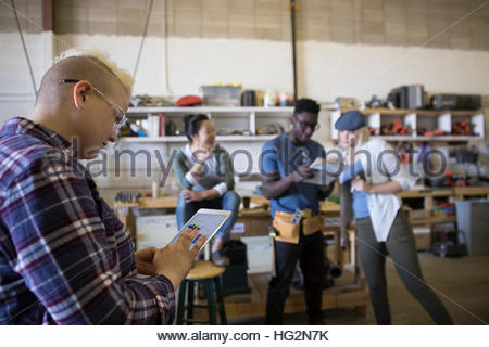 Female design professional engineer using digital tablet in workshop - Stock Photo