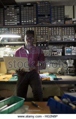 Portrait confident male electronics engineer using laptop in workshop - Stock Photo
