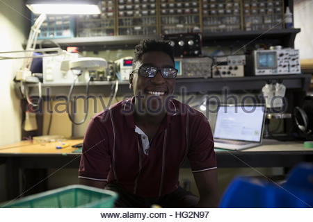 Portrait smiling male electronics engineer in workshop - Stock Photo