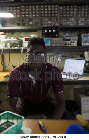 Portrait confident male electronics engineer in workshop - Stock Photo