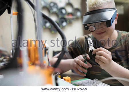Female electronics engineer with pliers at 3d printer in workshop - Stock Photo