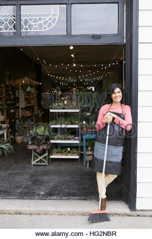 Portrait smiling female shop owner with broom standing in doorway of plant shop - Stock Photo