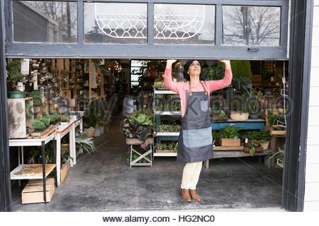 Female shop owner opening garage door in plant shop - Stock Photo