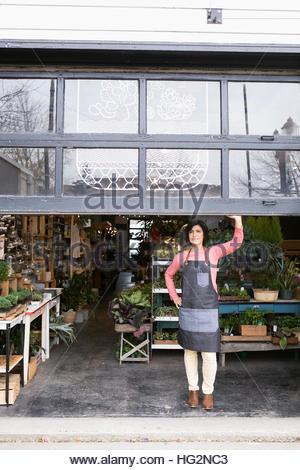 Portrait female shop owner opening garage door in plant shop - Stock Photo