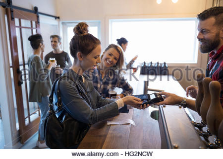 Female friends paying bartender for beers with smart phone contactless payment in brewery tasting room - Stock Photo