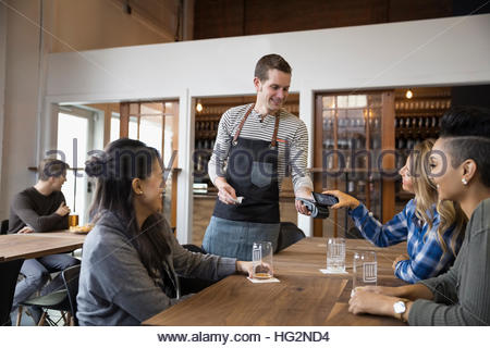 Female friends paying waiter with smart phone contactless payment in brewery tasting room restaurant - Stock Photo