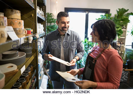 Female shop owner helping male customer shopping in plant shop - Stock Photo