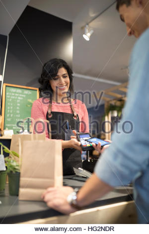 Female shop owner helping male customer paying with smart phone contactless payment at plant shop counter - Stock Photo