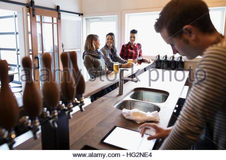 Women drinking beer at bar behind male brewer using digital tablet in brewery tasting room - Stock Photo