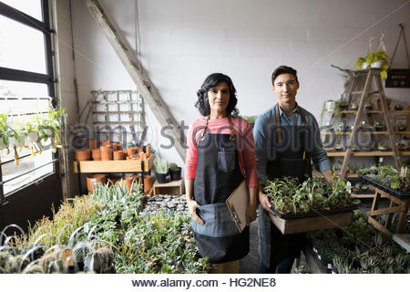 Portrait confident shop owners holding tray of potted plants in plant shop - Stock Photo