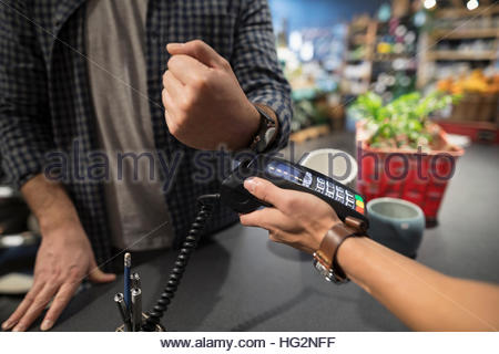 Close up male shopper paying with smart watch contactless payment at plant shop - Stock Photo