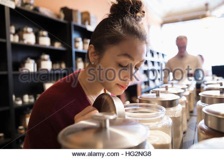 Female customer smelling spices in jars in spice shop - Stock Photo
