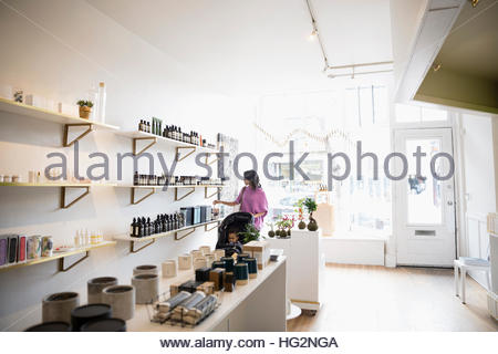 Mother and son shopping browsing merchandise on shelves in home fragrances shop - Stock Photo