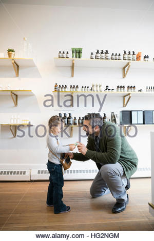 Father helping daughter with money shopping in home fragrances shop - Stock Photo