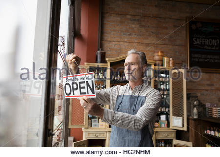 Male shop owner hanging open sign in spice shop window - Stock Photo