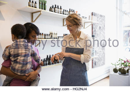 Female shop owner helping mother and son browsing beauty products in shop - Stock Photo
