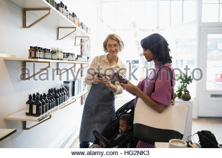 Female shop owner helping mother and son with home fragrances in shop - Stock Photo
