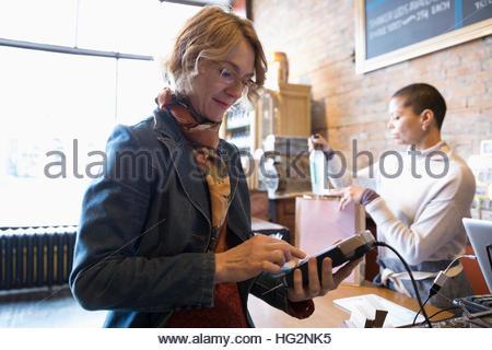 Female customer using pin entry credit card reader at shop counter - Stock Photo