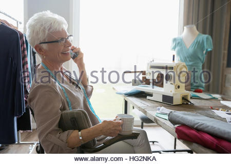 Smiling senior woman seamstress drinking coffee and talking on cell phone in home office - Stock Photo
