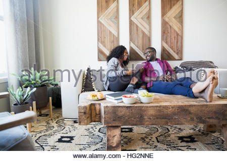 Couple talking using digital tablet on living room sofa - Stock Photo