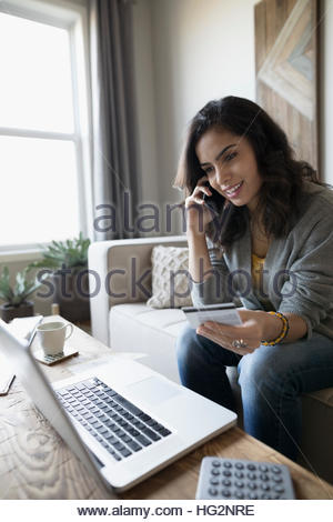 Smiling young woman at laptop holding credit card and talking on cell phone in living room - Stock Photo