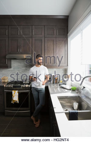 Pensive man drinking coffee and using cell phone in kitchen - Stock Photo