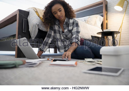 Teenage girl with laptop using calculator managing personal finances on bedroom floor - Stock Photo