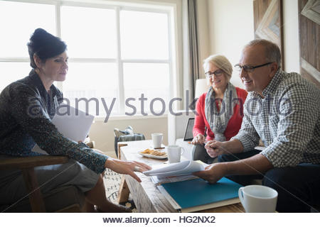 Financial advisor discussing paperwork meeting with senior couple in living room - Stock Photo
