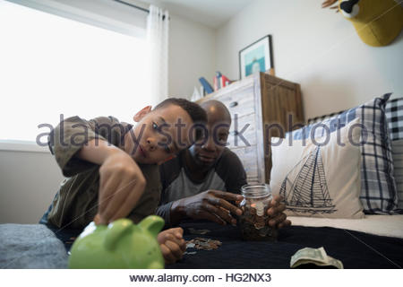 Father and son depositing coins into piggy bank in bedroom - Stock Photo