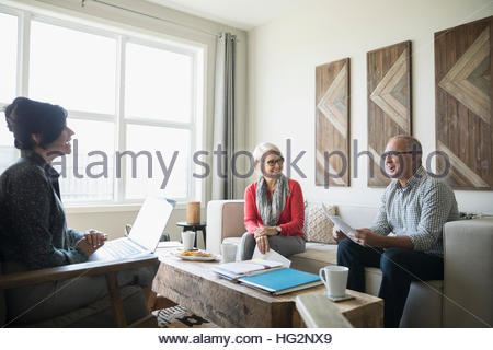 Financial advisor with laptop meeting with senior couple in living room - Stock Photo