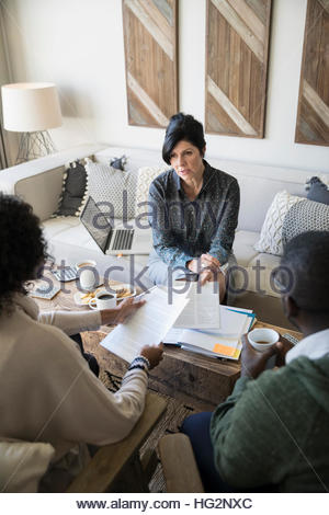 Financial advisor with paperwork meeting with couple in living room - Stock Photo